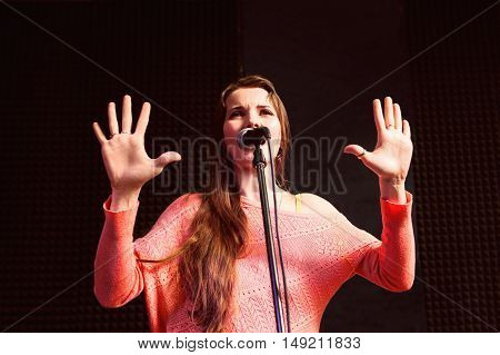 Young protesting woman on stage with microphone. Pretty woman screaming into mic, hands rised in stop gesture. Violently protesting young beautiful woman on stage