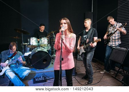 Musical band performance, hobby, leisure. Group of young adults playing music in studio. Hobby, leisure, pastime concept