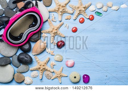 Diving mask with starfish and shells on blue wooden background