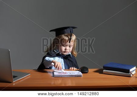 Little boy child smiling in black academic mantle and squared cap sitting at school wooden desk holding mark near notebook computer mouse and diaries