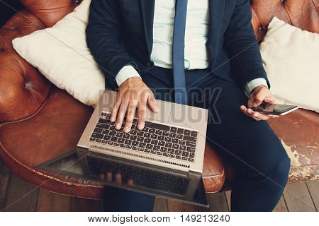 Unrecognizable man searching for new job sitting with laptop on his knees. Looking for vacancies online. Seeking for new workplace.