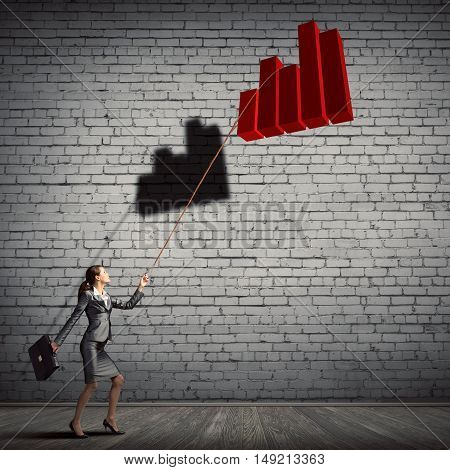 Elegant businesswoman with suitcase holding graph on lead