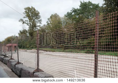 Temporary metal mesh along the road on the forest background