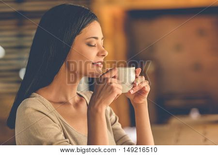 Beautiful girl is enjoying the aroma of coffee and smiling while resting in cafe