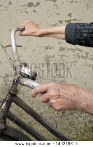 Elderly hands holding handlebar of a bicycle. Selective focus with shallow depth of field.
