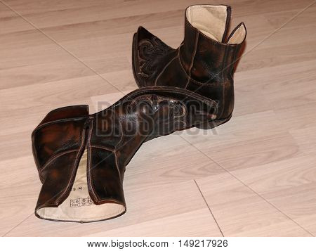 Pair of old worn brown western boots on wooden floor,
