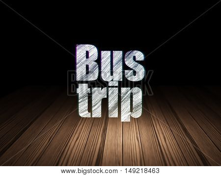 Tourism concept: Glowing text Bus Trip in grunge dark room with Wooden Floor, black background