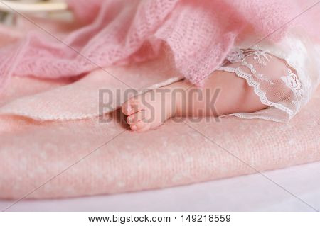Baby feet newborn. Sleeping baby foot on pink sheet of the bed