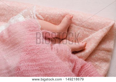 Baby feet newborn. Sleeping baby foots on pink sheet of the bed
