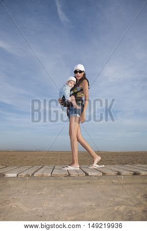 Baby In Rucksack With Shorts Mom