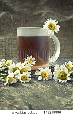 Cup of tea and chamomile flowers on a wooden table. Shallow depth of field.