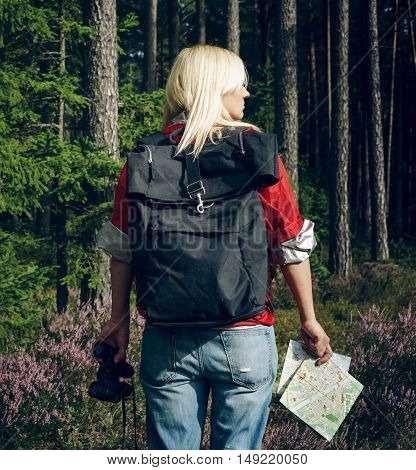 Young active woman tourist standing in a clearing in the woods with a backpack, holding binoculars and a map and looking at the forest. Healthy active lifestyle concept. Tourism.