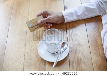 woman with white shirt ready to pay empty finished cappuccino coffee cup with made up credit card in hand on light brown wooden table cafe