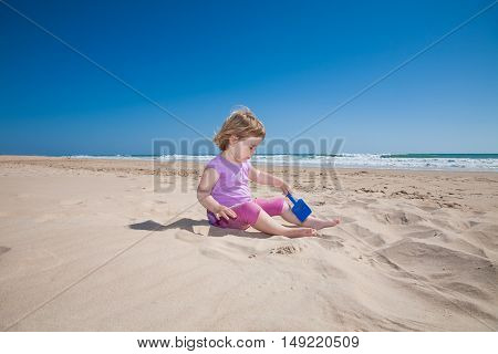 Little Girl Sitting Playing With Blue Shovel In Sand Beach