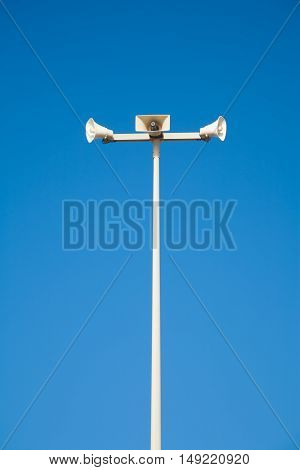 white metal tall pole with three megaphones over blue sky outdoor