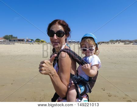 Thumb Up Mother And Baby In Backpack