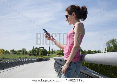 Woman Reading Phone In Footbridge