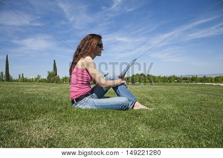 Woman Reading Tablet In Park