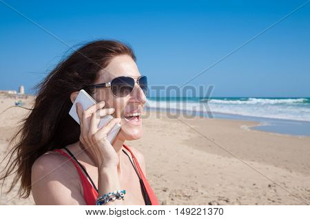 portrait of brunette woman looking side with sunglasses smiling and talking on mobile phone smartphone at beach with sea and blue sky behind