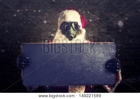 Scary Santa Claus holding blank chalkboard for ads