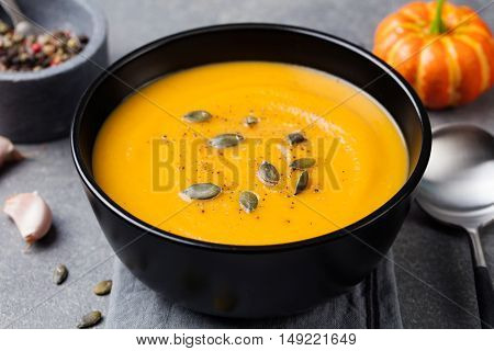 Pumpkin cream soup with pumpkin seeds in a black bowl. Grey stone background