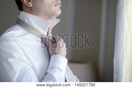 Groom is wearing a tie indoors. Male portrait of handsome guy. Beautiful model boy in colorful wedding clothes. Man is posing