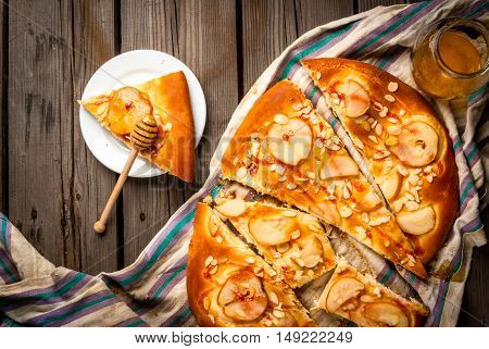 Freshly prepared fruit focaccia cake with pears and almonds on a rustic table with a towel, close - honey for pouring