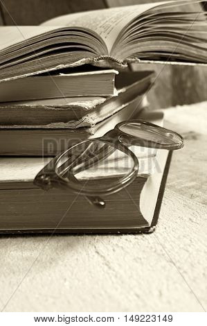 Old books with reading glasses. Selective focus on glasses.