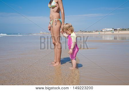 Baby And Mother Standing At Shore