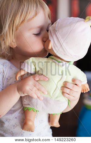 lovely and tender scene of blonde caucasian cute baby two years old kissing on the mouth a doll in hands indoor