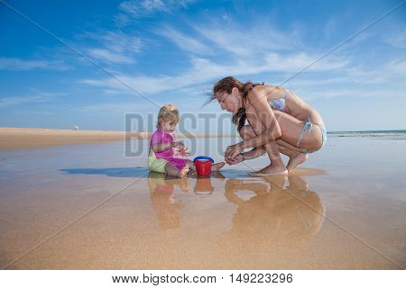 Baby Mother And Bucket At Beach