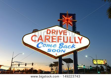 LAS VEGAS - DEC 25: Drive Carefully Come Back Soon on the back of the famous Sign of Welcome to Fabulous Las Vegas at dusk on Las Vegas Strip on Dec. 25, 2015 in Las Vegas, Nevada, USA.