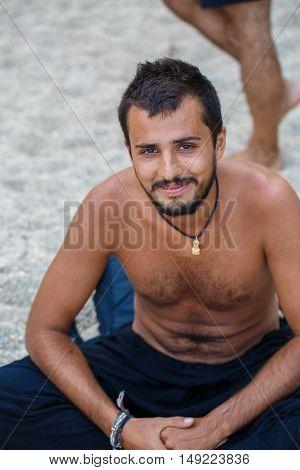 Man sitting on the white sand beach