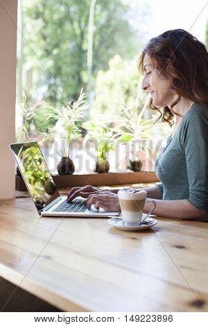 Green Shirt Woman Typing Laptop