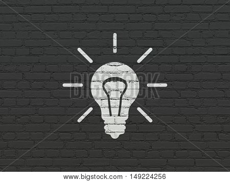 Finance concept: Painted white Light Bulb icon on Black Brick wall background