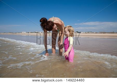 Smiling Baby And Mother At Ocean