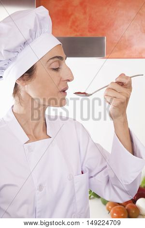 portrait of chef woman with professional jacket and hat tasting red sauce or cream puree like tomato ketchup in a steel soup spoon in her hand
