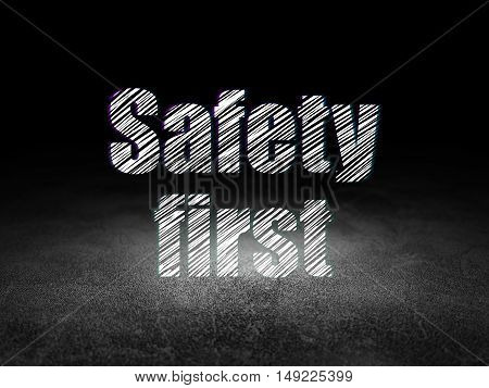 Privacy concept: Glowing text Safety First in grunge dark room with Dirty Floor, black background