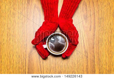 Woman hands in mittens holding a cup of coffee on wooden background