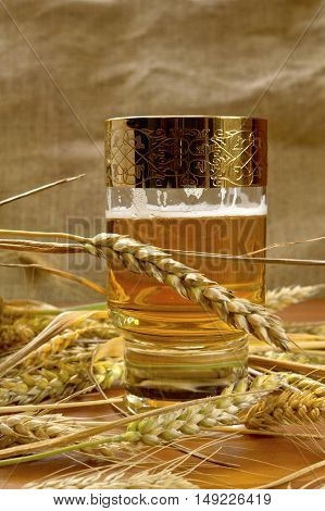 Glass of beer with barley on table.