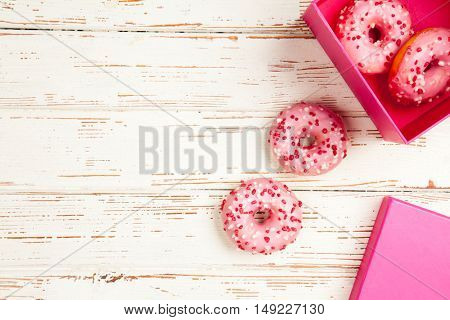 Tasty donuts on white wood background