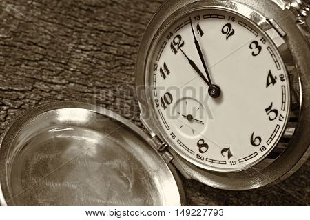 Time concept - Vintage pocket watch on weathered wood background