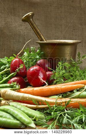 Tasty fresh vegetables with old bronze mortar.