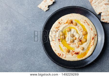Hummus, chickpea dip, with spices and pita, flat bread in a black plate on grey stone background. Copy space Top view
