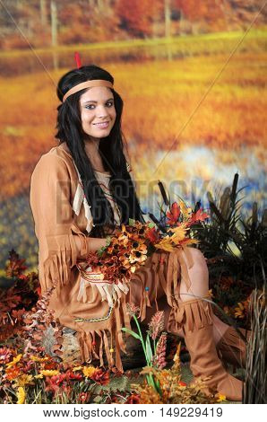A beautiful teen Indian relaxed on an old stump in autumn wetlands.