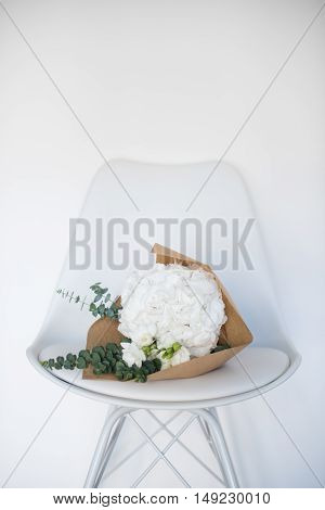 Bouquet of white hydrangeas on a chair by the wall