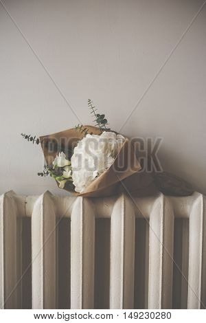 Bouquet of white hydrangeas on the heating radiator, vintage style