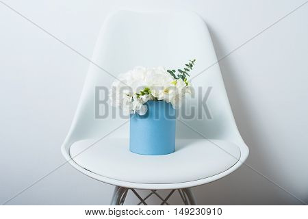 Bouquet of white hydrangeas in a box on a chair by the wall