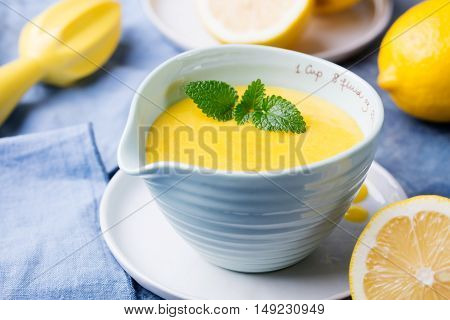 Lemon curd in ceramic bowl with fresh lemons on a blue napkin background Selective focus