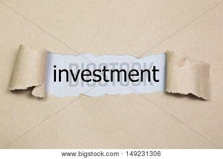 investment word written under torn paper, torn paper